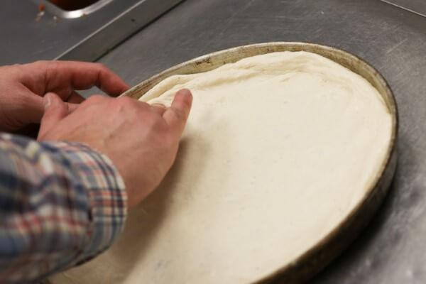 pressing dough into pizza pan
